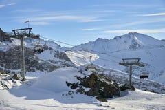 冬天在山之间的手段和滑雪倾斜在背景 图库摄影
