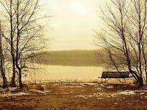 冬天在湖的老保守日落,冷的橙色太阳发出光线在水面上的水平之间。在地面上的熔化第一雪。 免版税库存图片