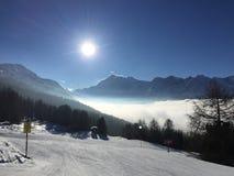 冬天场面滑雪倾斜 太阳和云彩在积雪的山 免版税库存照片