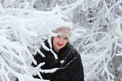 冬天外套和帽子的女孩在冬天森林里 免版税库存图片