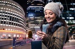 冬天外套的妇女有巧妙的电话的在夜城市 免版税图库摄影