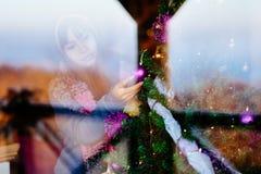 冬天外套的年轻美丽的亚裔妇女,在家装饰圣诞树 少妇画象射击低谷窗口 库存照片