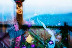 冬天外套的年轻美丽的亚裔妇女,在家装饰圣诞树 少妇画象射击低谷窗口 库存图片