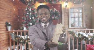 冬天外套的非裔美国人的黑人Â伸向前拿着有礼物的手一个箱子 股票录像