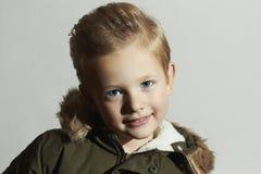 冬天外套的滑稽的时兴的孩子 方式孩子 孩子 卡其色的附头巾皮外衣 男孩微笑的一点 发型 免版税库存图片