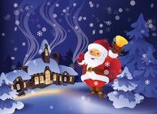 冬天多雪的夜在圣诞节村庄 有礼物袋子和响铃的圣诞老人在手中 免版税库存照片