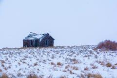冬天大草原的一个老被放弃的仓前空地 库存照片