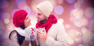 冬天夫妇的综合图象拿着杯子的 库存照片