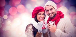 冬天夫妇的综合图象拿着杯子的 图库摄影