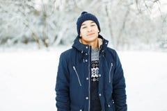 冬天夹克和毛线衣的英俊的人走 免版税库存图片