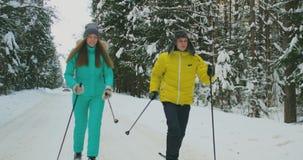 冬天夹克滑雪的微笑的人在慢动作的森林与他爱恋的妻子 健康生活方式 夫妇年轻人 股票录像