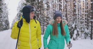 冬天夹克滑雪的微笑的人在慢动作的森林与他爱恋的妻子 健康生活方式 夫妇年轻人 影视素材