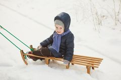 冬天夹克的小女孩坐爬犁在多雪的森林里 免版税库存照片