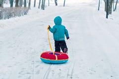 冬天奔跑的一个小男孩沿单独雪道 孩子拉扯雪撬 图库摄影