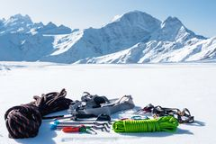 冬天套冰登山人的设备有carabiner创伤和一个阵营热水瓶的以积雪覆盖为背景 库存照片