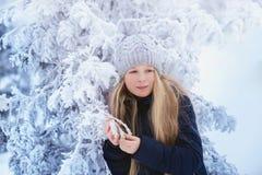 冬天女孩吹的雪 秀丽快乐的少年式样女孩获得乐趣在冬天公园 笑美丽的女孩户外 享受n 图库摄影