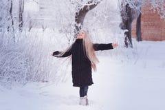 冬天女孩吹的雪 秀丽快乐的少年式样女孩获得乐趣在冬天公园 笑美丽的女孩户外 享受n 免版税库存照片