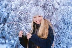冬天女孩吹的雪 秀丽快乐的少年式样女孩获得乐趣在冬天公园 笑美丽的女孩户外 享受n 免版税库存图片