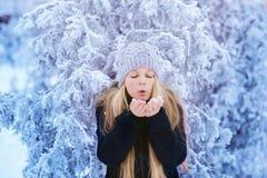 冬天女孩吹的雪 秀丽快乐的少年式样女孩获得乐趣在冬天公园 笑美丽的女孩户外 享受n 免版税图库摄影