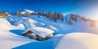 冬天妙境在有传统山小屋的阿尔卑斯在日落 免版税库存照片