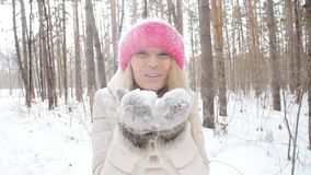 冬天娱乐的概念 获得的少妇吹从她的手的乐趣新鲜的雪 股票录像