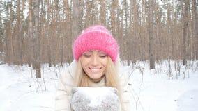 冬天娱乐的概念 获得的少妇吹从她的手的乐趣新鲜的雪 影视素材