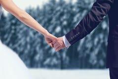 冬天婚礼夫妇新娘和新郎藏品移交多雪的森林背景 免版税库存图片