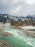 冬天季节的村庄古色古香的鲜绿色河 免版税库存图片