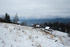 冬天季节的空的牧羊人房子有多云阴暗天空背景  免版税库存照片