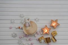 冬天季节食物和饮料与热的泡沫的饮料和熔化的蛋白软糖的摄影图象在雪人形状用巧克力 图库摄影