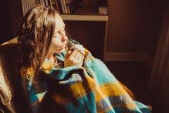冬天寒冷概念 温暖结冰的手的舒适的椅子的年轻结冰的妇女包裹在温暖的蓬松羊毛格子花呢披肩毯子 库存图片
