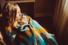 冬天寒冷概念 舒适的椅子的年轻结冰的妇女呼吸在温暖的蓬松羊毛pla包裹的冻结的手上的温暖的空气 库存图片