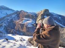 冬天山的自然摄影师 免版税库存图片