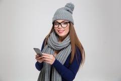 冬天布料的妇女使用智能手机 免版税库存照片