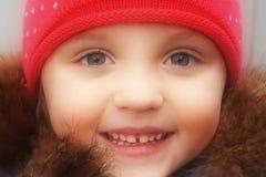 冬天帽子和夹克的美丽的愉快的面孔女孩 免版税库存照片