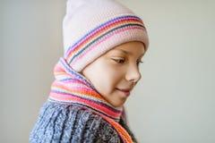 冬天帽子和围巾的小美丽的女孩 免版税库存照片