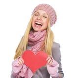 冬天帽子和围巾的愉快的女孩有心形的明信片的 库存图片