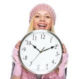 冬天帽子掩藏的看的微笑的少年女孩从时钟 免版税库存图片