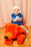 冬天帽子的一个小男孩坐玩具负担 库存照片
