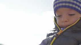 冬天帽子的一个美丽的小孩,使用在与玩具的海滩 影视素材