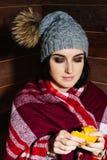 冬天心情  帽子和穿戴干净的普通话的年轻美丽的微笑的妇女在木背景 图库摄影