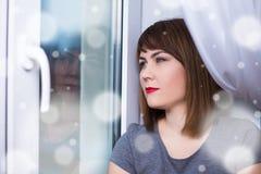 冬天悲伤-坐由窗口的美丽的作的妇女 免版税图库摄影