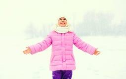 冬天愉快的微笑的小女孩孩子享用在雪的雪花 免版税库存图片