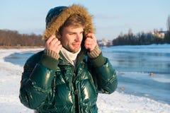 冬天成套装备 行家冬天时尚成套装备 人有敞篷的穿戴夹克在冷淡的冬日 温暖人有胡子的立场 免版税库存图片