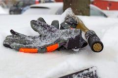 冬天手套和雪刷子在一辆积雪的汽车顶房顶特写镜头 库存照片