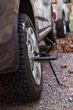 冬天散布了轮胎在汽车的轮子架置有螺旋千斤顶的秋天 免版税库存图片