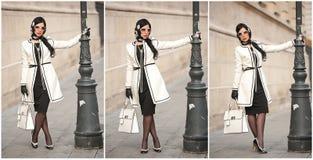 冬天方式射击的可爱的少妇 摆在大道的黑白成套装备的美丽的时兴的女孩 免版税库存图片