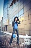 冬天方式射击的可爱的少妇 黑皮革的美丽的时兴的女孩与大帽子和蓝色提包 免版税库存图片