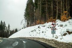 冬天旅行乘汽车通过山口 一个锋利的轮和警告路标在路在山 免版税库存图片