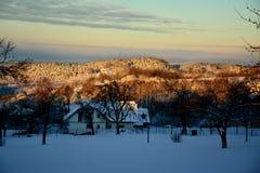 冬天日出的森林与房子 免版税库存图片
